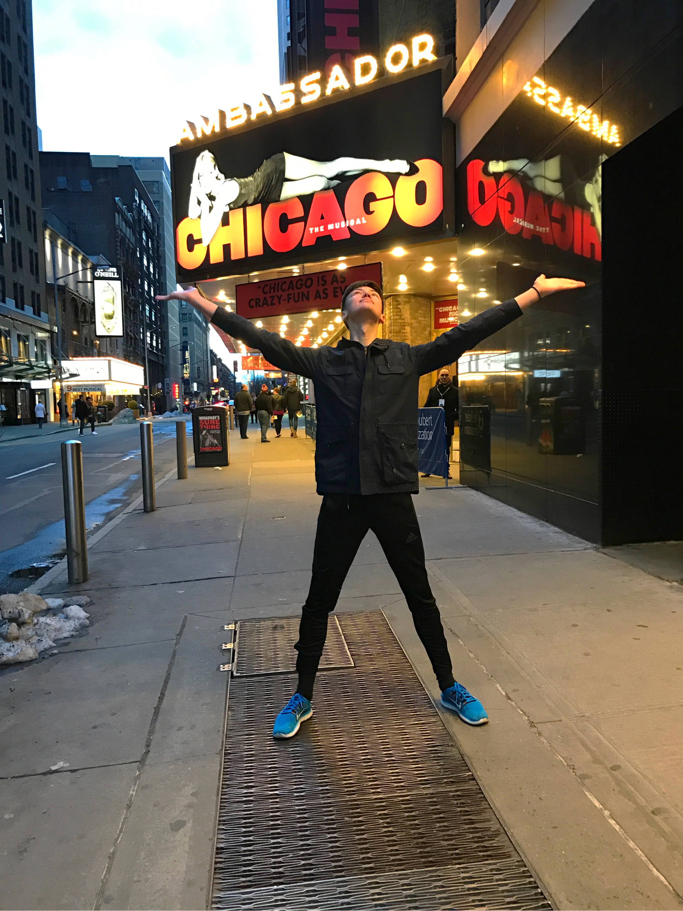 "William Brickhouse poses in front of a sign for the iconic production ""Chicago."""