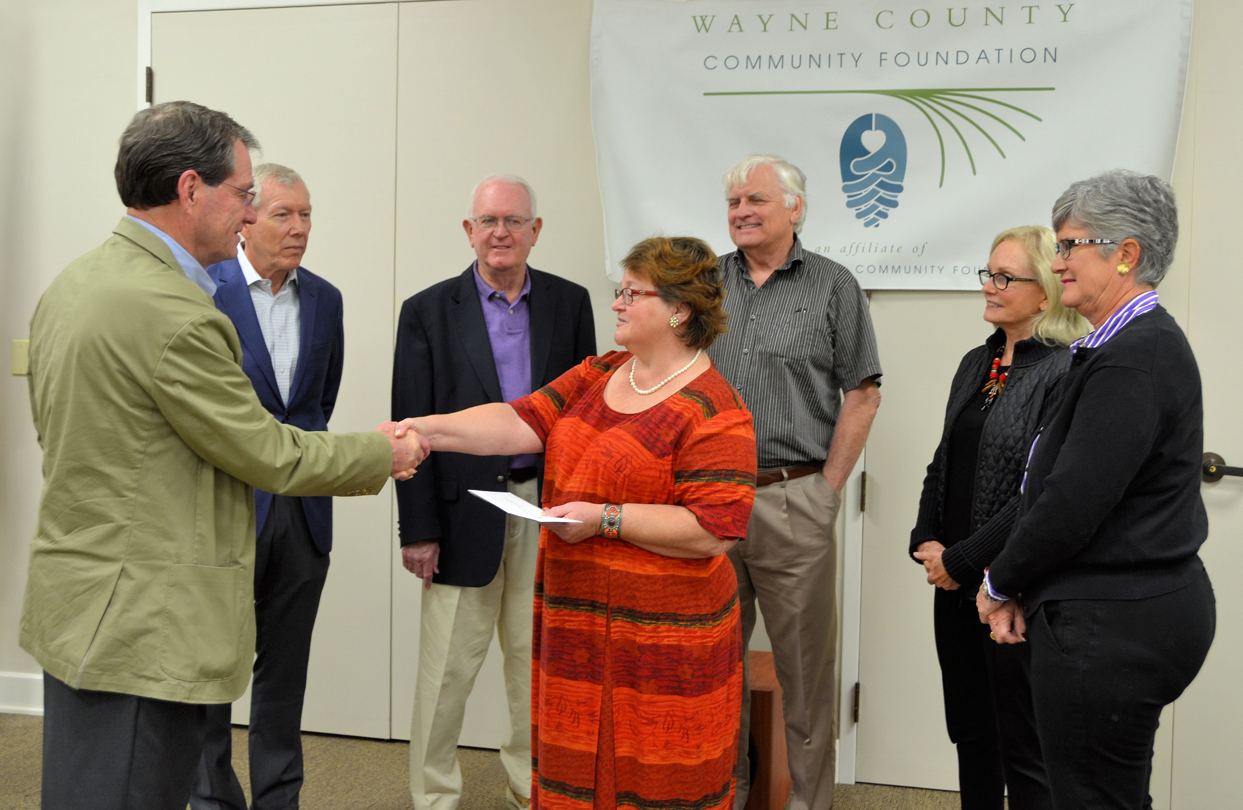 Bob Logan, president of the Wayne County Community Foundation, presents a check from NCCF's Disaster Relief Fund to Barbara Stiles of Wayne County's Long Term Recovery Group.